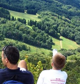 A father and son survey the valley from their campsite.