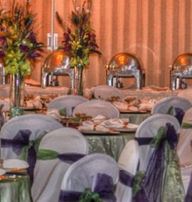 A decadent dining hall decorated with colorful flowers and ribbons.