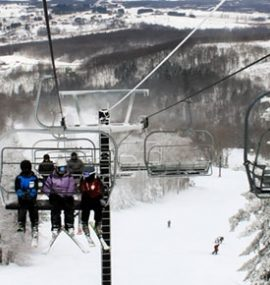 A group of skiers rides the lift through snow-covered forest.